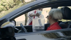 Focus on restaurant worker as he puts this woman's curbside food order through the passenger window of her car.