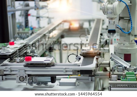 Focus on robotic arm's gripper. Industry 4.0 concept; artificial intelligence in smart factory. Robot picks up the product from automated car on the manufacturing line. Selective focus.