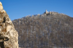 Focus on Rock. Castle also Stronghold (Teck) in winter on a clear evening with blue sky, many trees on the hill, rock in the foreground. Germany, Owen, Swabian alb.