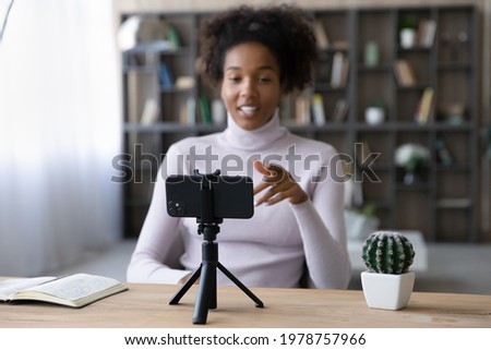 Focus on smartphone standing on table on tripod stabilizer, recording african american female blogger. Smiling pretty young mixed race woman influencer filming educational video on phone web camera.