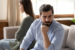 Focus on stressed thoughtful young man sitting separate from offended wife on couch at home. Young frustrated married family couple ignoring each other after quarrel, relations problems concept.