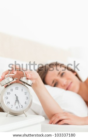 focus on the clock as the woman uses her hand to turn the alarm off.