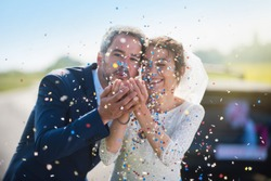 Focus on the confetti. portrait of newlyweds. the groom blowing on confetti and the bride smiling. their hands meet. the focus is on them while their car with just married is blur. shot with flare