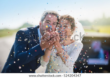 Focus on the confetti. portrait of newlyweds. the groom blowing on confetti and the bride smiling. their hands meet. the focus is on them while their car with just married is blur. shot with flare #524204347