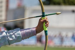 Focus on the manicured sparkly nails and arm enrobed in elaborate national dress of a lady archer taking aim with a bow and arrow on the Archery Field at the Naadam Festival in Ulan Bator in Mongolia