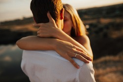 Focus on the woman's hand with engagement ring. Young wedding couple kissing in the field. Woman hugs man and kisses each other.