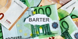 Focus on the word BARTER on piece of torn white paper with EUROS currency as a background. Concepts of business.