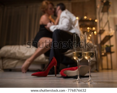 Focus on two glasses of champagne on floor. Ardent loving couple is sitting on bed and hugging with passion on background. Romantic date concept