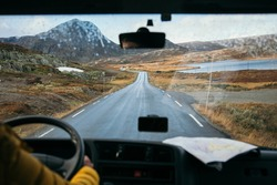 Focus on view from inside adventure car or camper van on amazing cinematic scandinavian landscape. Travel on epic road trip through mountains. Nomadic vanlife lifestyle. Life on the road