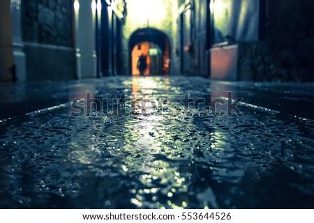 Focus on wet ground along dark medieval alley on a rainy night, Butter Slip, Kilkenny Ireland.