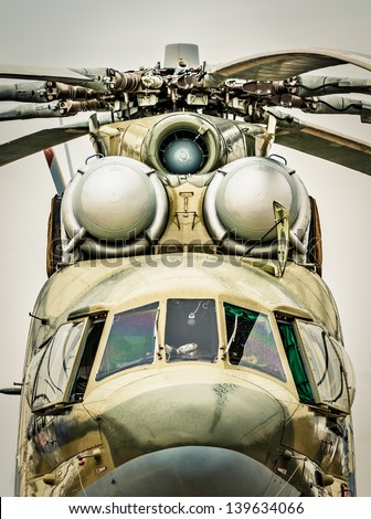 Focus on windows of cockpit and propeller of russian military helicopter, gray sky in background. Army air transport in Russia. Front view of chopper outdoors. Modern, beautifully designed helicopter.