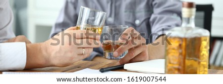 Focus on workers hands holding glass of whiskey. Colleagues sitting at table with documents and drinking alcohol. Businessman celebrating success or worrying problem