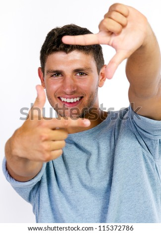 Focus on young man making frame with his hands - stock photo
