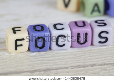 Focus wording from alphabet beads on a wooden surface. selective focus #1443838478
