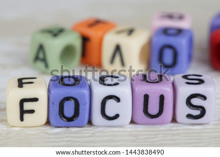 Focus wording from alphabet beads on a wooden surface. selective focus #1443838490