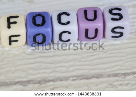 Focus wording from alphabet beads on a wooden surface. selective focus #1443838601