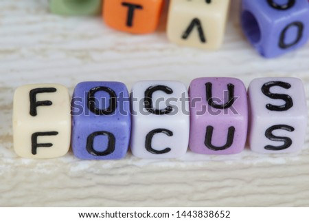 Focus wording from alphabet beads on a wooden surface. selective focus #1443838652
