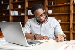 Focused African-American guy is using a laptop for watching webinars, taking notes, studying online. A male freelancer writes down startup ideas, sittin at the desk in office