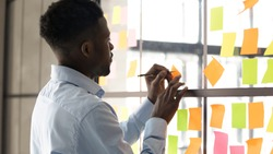 Focused African American male employee write on colorful sticky notes develop business project in office, concentrated biracial man worker brainstorm engaged in creative thinking make startup plan