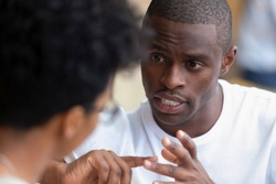 Focused african american man looking speaking to woman having business talk negotiating explaining, serious black guy having conversation with girlfriend friend discussing important issues at meeting