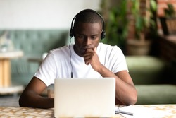 Focused African American man wear headphones, using laptop, looking at computer screen, thoughtful black student watching video, webinar, learning languages, studying online, making video call