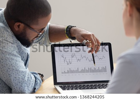 Focused african analyst showing client or colleague annual financial report analyzing business data on laptop screen using software for digital graphic statistic analysis, economic market graphs
