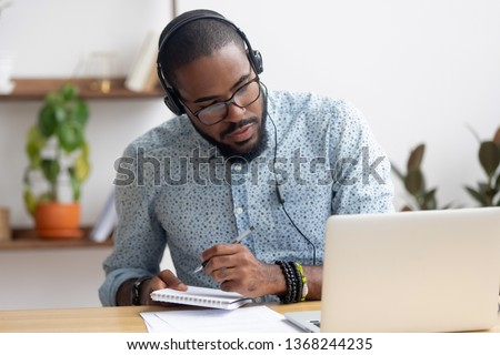 Focused african business man in headphones writing notes in notebook watching webinar video course, serious black male student looking at laptop listening lecture study online on computer e learning #1368244235