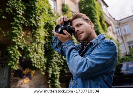 Photo of Focused and confident professional photographer, handsome man stylish hipster freelancer works remotely on the street, takes a picture. People lifestyle, creative profession.