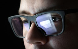 Focused and thoughtful man. Coder, programmer or developer using laptop in dark. Businessman working late. Student studying at night. Close up of glasses with reflection of computer screen.