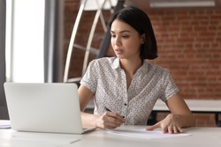 Focused asian business woman working studying online in office looking at laptop making notes, serious japanese employee or student watching webinar writing information in notebook sitting at desk