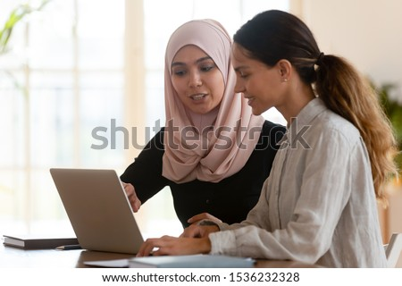 Focused asian muslim female mentor teacher teach caucasian intern worker learning new skills explaining computer software work together at modern workplace, apprenticeship internship course concept