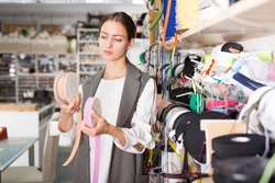 Focused attractive girl choosing colored textile ribbons for needlecraft in store..