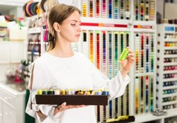 Focused attractive girl choosing natural threads for needlecraft in store..