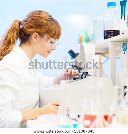 Focused attractive young life science professional measuring the absorbance of the solution in cuvette in the spectrophotometer. Focus on the researcher's face.