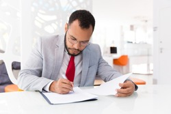 Focused auditor checking document. Business man wearing suit and eyeglasses, signing contract. Document expertise concept