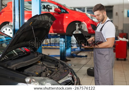 Focused auto mechanic working on a computer connected to a car engine
