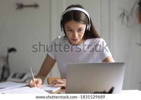 Focused beautiful young woman student in headphones looking at computer screen, listening to educational lecture webinar or video conference, making notes in copybook, distant education concept.