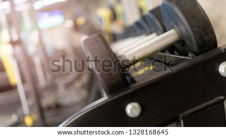 Focused black dumbbell set with blurred background of gym. Close up many metal dumbbells on rack in sport fitness center. Weight training equipment concept.