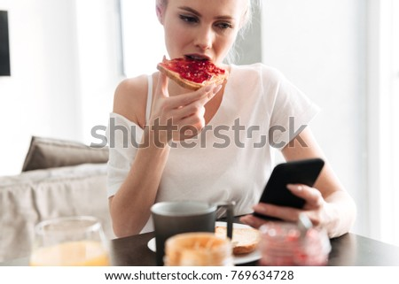 Focused blonde lady eating bread with jam amd using smartphone while have breakfast in kitchen