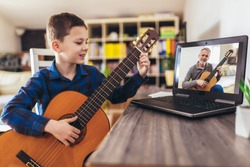 Focused boy playing acoustic guitar and watching online course on laptop while practicing at home. Online training, online classes.