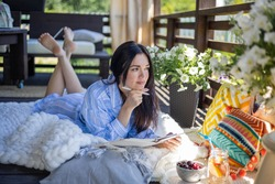 Focused brunette woman thinking imagination with pen and notepad at nature summer outdoor village terrace. Pensive Asian female taking notes writing paper diary relaxing on balcony countryside house