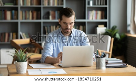 Focused business man sit at workplace desk at home office cozy room working on laptop, make analysis sales stats results, learn graphs and making financial forecasts. Busy workday, modern tech concept