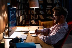 Focused business man trader analyst looking at computer monitor, investor broker analyzing indexes, financial chart trading online investment data on cryptocurrency stock market graph on pc screen.