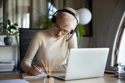 Focused business woman in glasses wearing headset with microphone sitting at desk, listening to educational lecture on laptop, learning studying remotely alone online at workplace, writing notes,