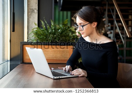 Focused business woman sit on cafe working on laptop, concentrated serious female working with computer and notebook in coffee shop, freelancer, studying online, browse internet, checking bills