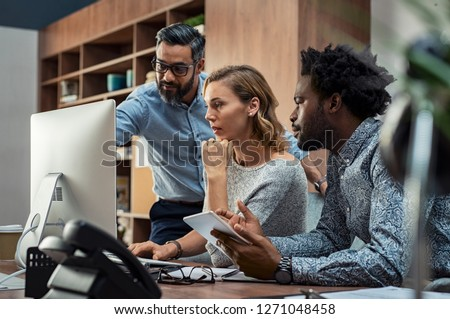 Focused businesspeople discussing project while looking at computer screen. Mature manager working with his creative team in a modern office. Multiethnic casual teamwork at work. #1271048458