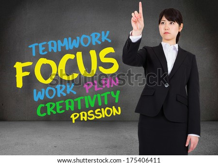 Focused businesswoman pointing against buzz words in room