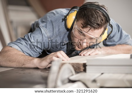 Focused carpenter at work with wooden plank