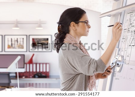 Focused casual caucasian female architect working at drawing board with pen in hand. Wearing glasses, at office. Floor plan, busy, concentration, unsmiling. #291554177