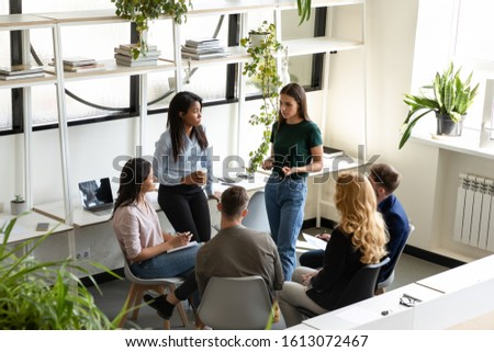 Focused concerned diverse office employees gather together in modern light co-working space deliberating, discussing risks, solve business common problems, teamwork and partnership, brainstorm concept